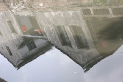 Den gamla stenen inhyser reflexion på floden Royaltyfria Bilder