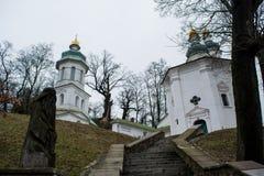 Den gamla stora vita forntida kristna kyrkan med kors, det gröna taket och förebilden sned från wood near trappa Arkivfoton