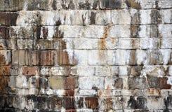 Den gamla strimmiga stenväggen med fuktiga fläckar och encrusted vit ytbehandlar Royaltyfri Foto