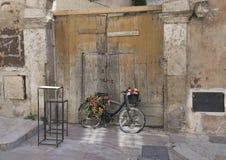 Den gamla svarta cykeln vände in i en blommaskärm i Matera, Italien Royaltyfri Fotografi