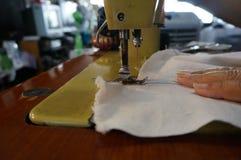 Den gamla symaskinen syr torkduken Arkivfoto