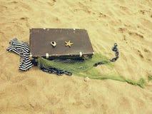Den gamla tappningresväskan för lopp- och familjsemestrar ligger på stranden Hav för havskust Foto i en moderiktig retro stil arkivfoto
