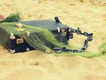 Den gamla tappningresväskan för lopp- och familjsemestrar ligger på stranden Hav för havskust Foto i en moderiktig retro stil royaltyfria bilder