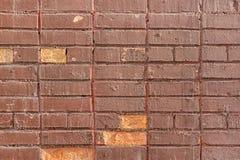 Den gamla tegelstenväggen målas med brun målarfärg Tom bakgrund med murverktextur arkivfoto