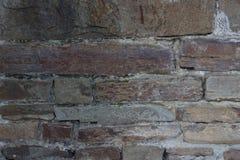 Den gamla tegelstenväggen texturerade mörka stenar av olika färgtegelstenar med cement arkivfoton