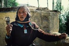 den gamla tibetana buddisten vallfärdar damen som går runt om kloster i traditionella klänning och smycken med en stämpel för den arkivbilder
