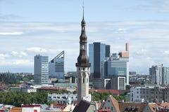 Den gamla tornspiran av det medeltida stadshuset på bakgrunden av den moderna staden estonia tallinn Arkivbild