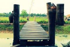Den gamla träbron som korsar den jordbruks- kanalen som dekoreras med bambu som fiskar hjälpmedel på kulturellt, parkerar arkivbild