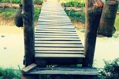Den gamla träbron som korsar den jordbruks- kanalen som dekoreras med bambu som fiskar hjälpmedel på kulturellt, parkerar royaltyfria foton