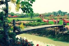 Den gamla träbron som korsar den jordbruks- kanalen som dekoreras med bambu som fiskar hjälpmedel på kulturellt, parkerar arkivfoto