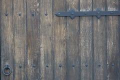Den gamla trädörren i stenar väggen från medeltida era Tappningmetallhänglås på en trädörr royaltyfria bilder