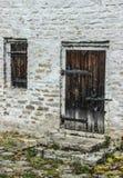 Den gamla trädörren med ett lås i en tegelsten övergav huset Arkivfoto