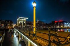 Den gamla träholländska bron på nattetid mot rusar moln Arkivfoto