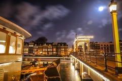 Den gamla träholländska bron på nattetid mot rusar moln Arkivfoton