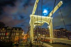 Den gamla träholländska bron på nattetid mot rusar moln Arkivbilder