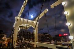 Den gamla träholländska bron på nattetid mot rusar moln Royaltyfri Bild