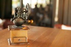 Den gamla träkaffekvarnen med handtaget shoppar in bakgrundsdesign Arkivbilder