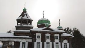 Den gamla träkyrkan i vinterdag står bland träd arkivfilmer
