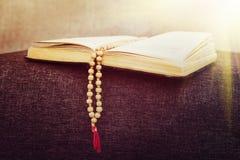 Den gamla träradbandet pryder med pärlor på en bok av ceremonier royaltyfri bild