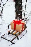 Den gamla träsläden med en gåva i guld- slåget in rött gåvaband för pappers- ask, är i vinterskogen, snö, träd nära Klottret utfo Arkivbild