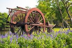 Den gamla trävagnen och lilor blommar i trädgård Royaltyfria Foton
