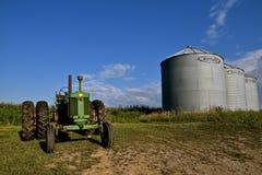 Den gamla traktoren för 720 John Deere parkerade tillsammans med Butler Bins Arkivbild