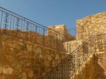 Den gamla trappuppgången byggs av gul tegelsten och dekoreras med openwork metallräcke som leder till en vägg fotografering för bildbyråer