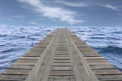 Den gamla träbron i havet och har den obetydliga vågen Arkivfoton