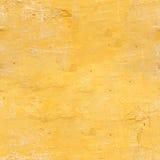 Den gamla väggen av lägenhethuset i gul färg Textur av den skalade yttersidan Royaltyfri Foto