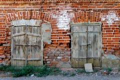 Den gamla väggen av röd tegelsten med två stängde fönster Fotografering för Bildbyråer