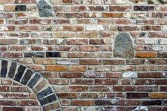 Den gamla väggen för röd tegelsten med granit stenar införing, bågen och blom Royaltyfria Bilder