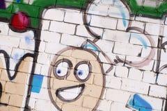 Den gamla väggen som målas i färggrafitti som drar röd ærosol, målar Bakgrundsbild på temat av teckningsgrafitti och gata a royaltyfri fotografi