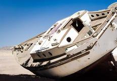 Den gamla yachten ligger på sanden i öknen mot den blåa himlen i Egypten Dahab södra Sinai royaltyfri bild