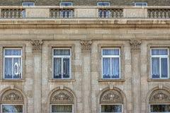 Den gamla yttre stenväggen med rad av fönster med snör åt gardiner Royaltyfria Foton