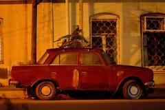 Den gamla Zhiguli bilen på natten under gatabelysning, med Mercedes rullar, i Baku, Azerbajdzjan royaltyfri fotografi