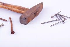 den gammal rosthalshammaren och rost spikar halsen som används på vita det isolerade bakgrundshjälpmedlet Arkivfoto