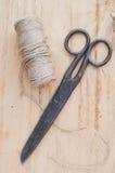 Den gammal saxen och skeinjute tvinnar på en träbakgrund, den selektiva fokusen, lantlig stil Arkivfoton