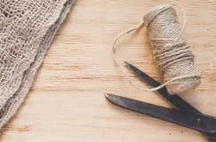 Den gammal saxen och skeinjute tvinnar på en träbakgrund, den selektiva fokusen, lantlig stil Royaltyfri Bild