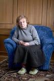 den gammala fåtöljen sitter kvinnan Royaltyfri Fotografi