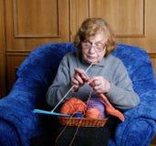 den gammala fåtöljen sitter kvinnan Fotografering för Bildbyråer