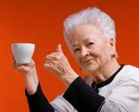 Den gammala kvinnan i exponeringsglas som tycker om kaffe, eller tea kuper Royaltyfri Foto