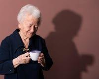 Den gammala kvinnan som tycker om kaffe, eller tea kuper Royaltyfria Bilder