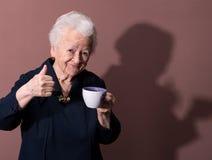 Den gammala kvinnan som tycker om kaffe, eller tea kuper Fotografering för Bildbyråer