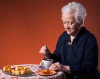 Den gammala kvinnan som tycker om tea, kuper med äpplepien Arkivbilder