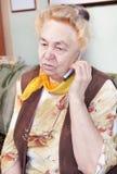 Den gammala kvinnan talar vid en mobil Arkivfoto