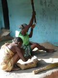 Den gammala kvinnan tröskar korn på henne farstubron Royaltyfri Foto