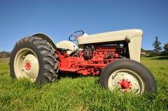 Den gammala lantgårdtraktoren i ett gräs sätter in Royaltyfria Bilder