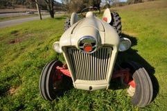 Den gammala lantgårdtraktoren i ett gräs sätter in Fotografering för Bildbyråer