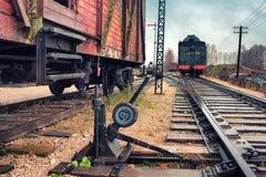 Den gammala lokomotivet och bilar på en järnväg posterar Fotografering för Bildbyråer