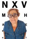 Den gammalare kvinnan med bordlägger för synar examen Arkivbild